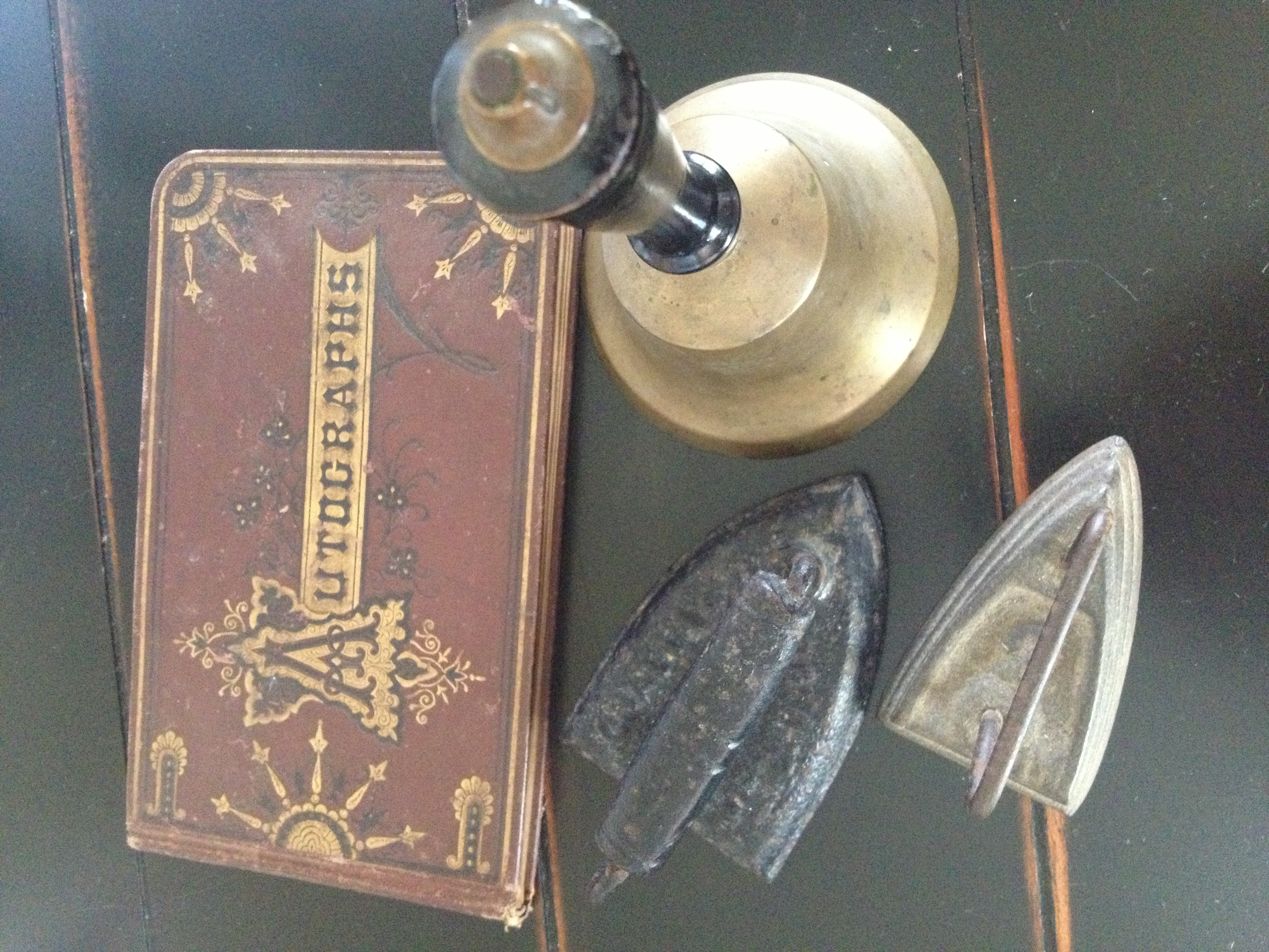 Antiques: an autograph book, a bell, and two irons.