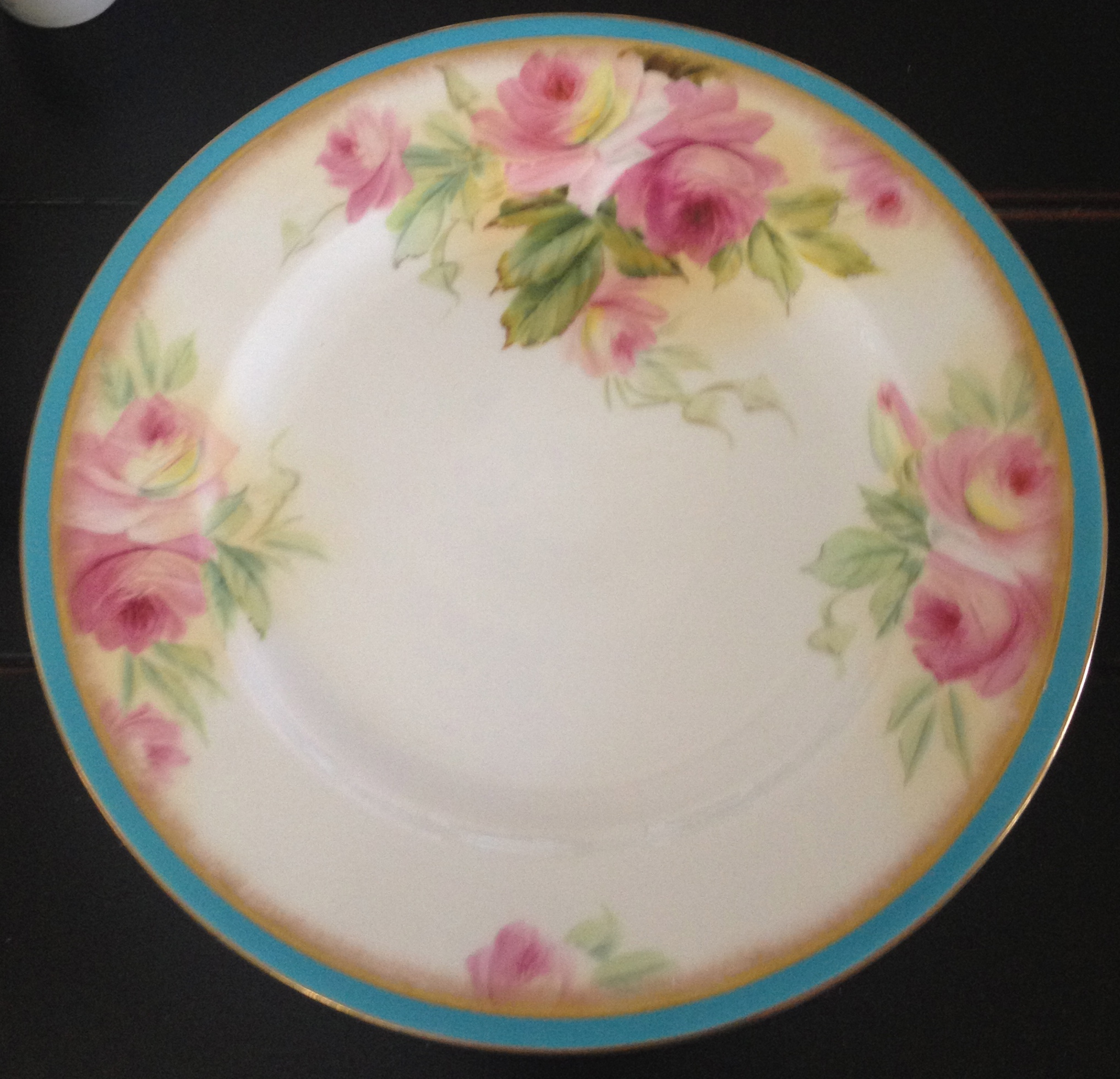 Vintage china with a turquoise and floral pattern.
